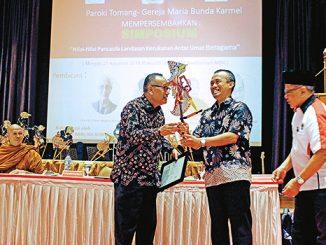 Romo Andy Priambada OCarm memberikan wayang kepada Achmad Syafii Mufid. [HIDUP/Stefanus P. Elu]